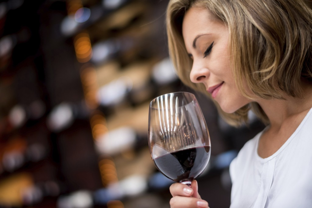 Woman tasting wine at a cellar smelling into a glass