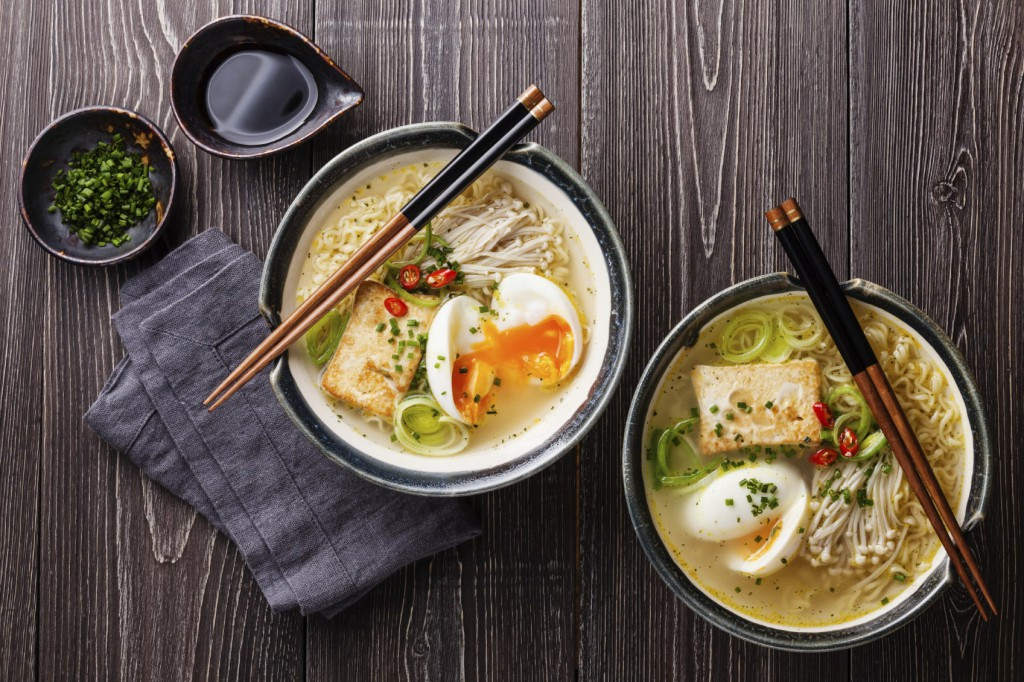 Asian Miso ramen noodles with egg, tofu and enoki in bowls on gray wooden background