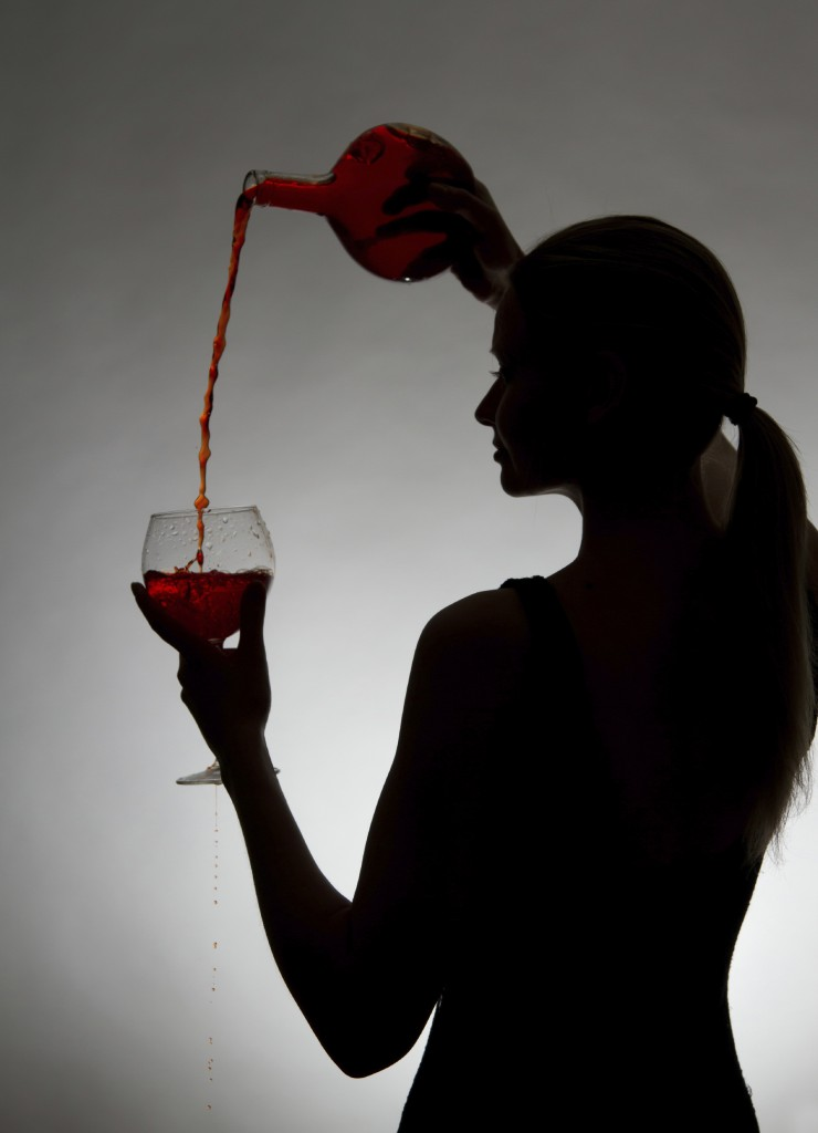 Woman pouring red wine from bottle into a glass on a gray background.
