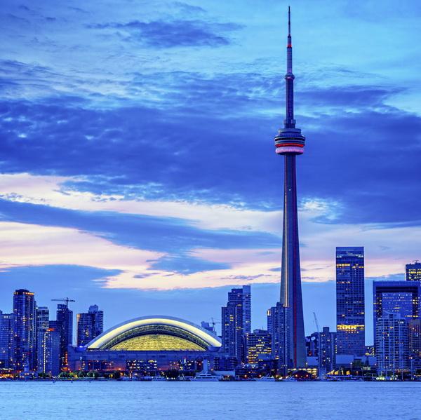 Toronto cityscape with CN Tower and baseball stadium at dusk