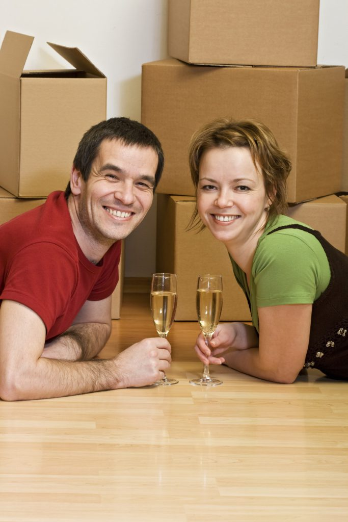 Couple toasting in their new home among cardboard boxes