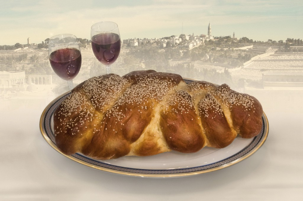 Homemade challa bread on plate with wine glasses on table fading to Jerusalem skyline in background