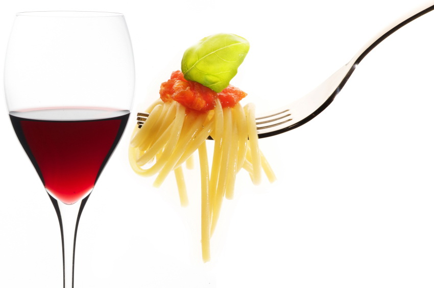 red wine glass and fork with spaghetti on white background