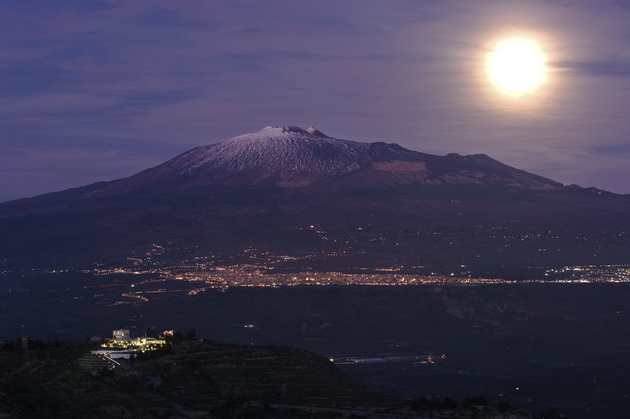 moonlight on the volcano Etna and night skyline of Adrano from Centurpe, Italy