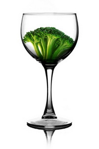 a glass of wine with a brocoli sprout