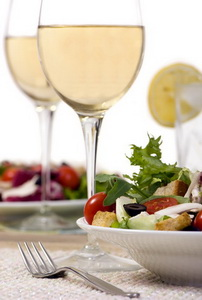 A health dinner salad with lots of greens and white wine