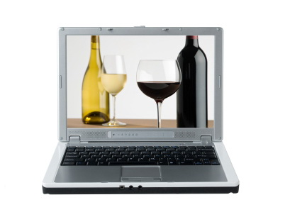 laptop computer with an image of wine bottles and wine glasses on the screen