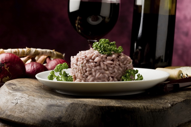 photo of delicious risotto with red wine on wooden table