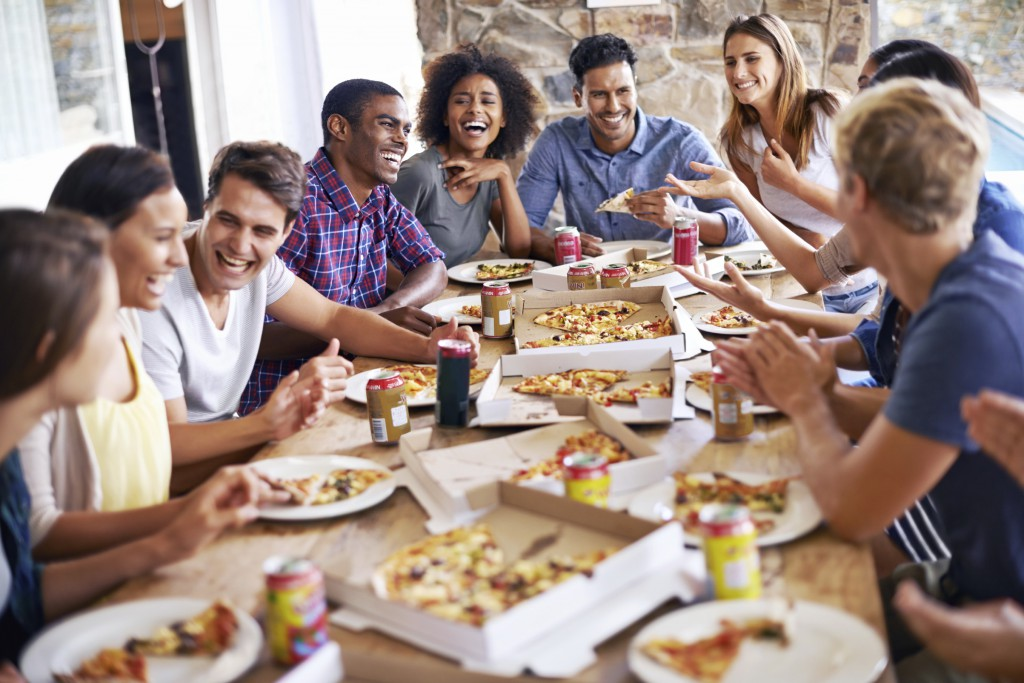 Cropped shot of a group of friends enjoying pizza together