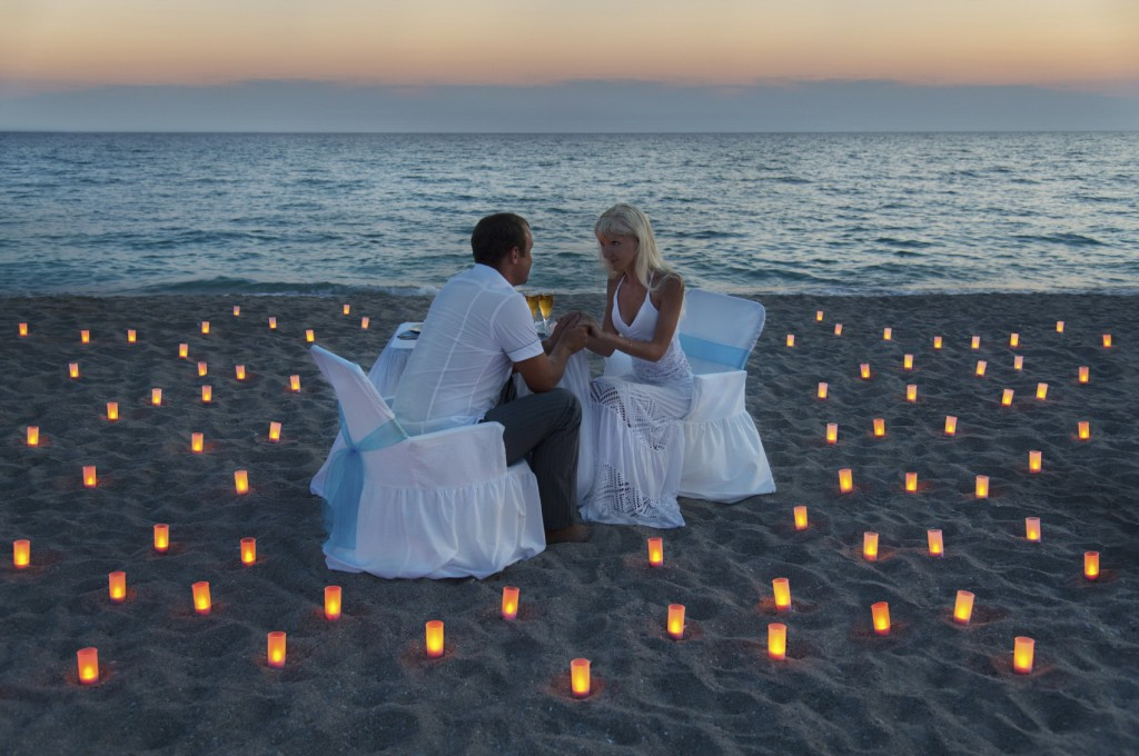 lovers couple share a romantic dinner with candles on sandy sea beach during sunset