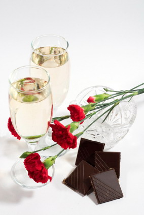 two glasses of champagne or white wine with crystal vase, carnation and chocolate tiles. White background with copyspace