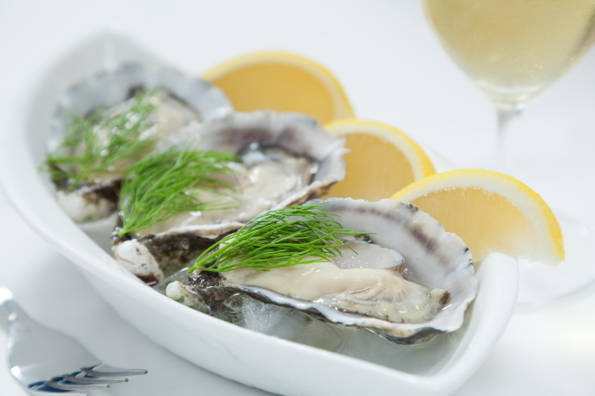 Fresh river oysters on ice with dill, lemon and wine