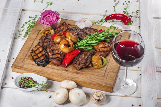 Grilled pieces of meat and different vegetables on wooden board