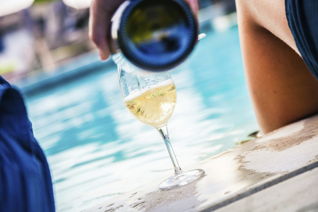 summer pool side pouring wine
